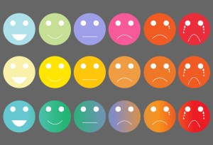 Multicolored graphic illustration of three rows of five face emojis, ranging from smiling on the left to crying on the right.