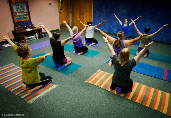 A small group of women of varied ages and sized bodies, wearing t-shirts and sweats, seated on colorful yoga mats with arms spread in a wide V. The teacher faces them, seated in front of a dark blue wall.