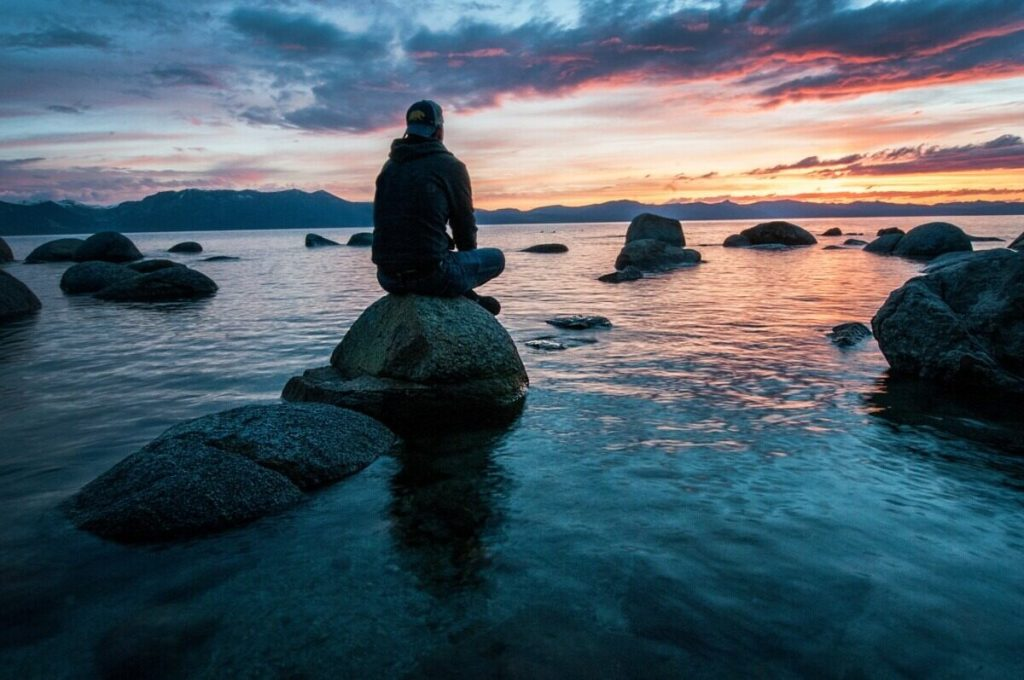 man sitting on rock surrounded by water