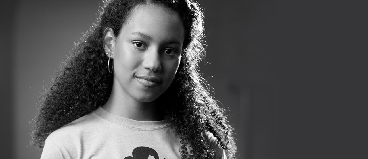 Minely, a National Gold Award Girl Scout, in a Girl Scout T-shirt in front of a grey background