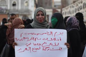 Photo of woman in a green hijab holding a sign with text in Arabic, with people in the background