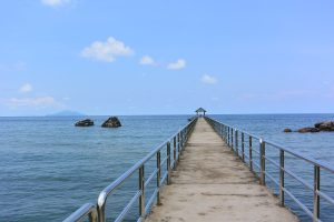 Cover photo for Using Conscious Entrepreneurship to Create Sustainable Change. Photo of a dock leading out into the blue sea, with a blue sky with a few white clouds.