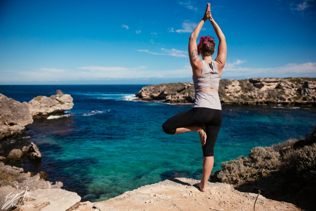 girl in yoga pose overlooking beautiful ocean, healthy fit travelling