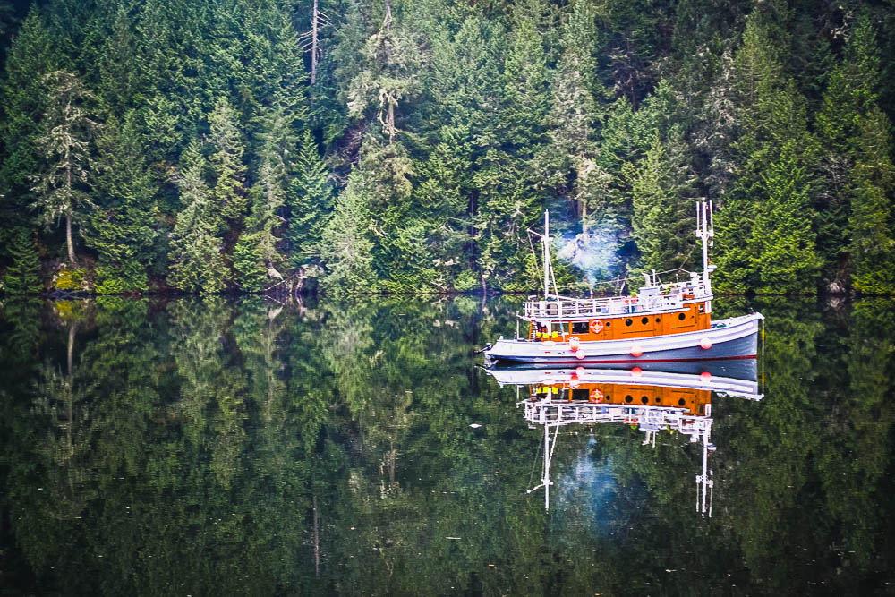 Perfect reflection of boat and woods in lake at gowlland tod provincial park vancouver island