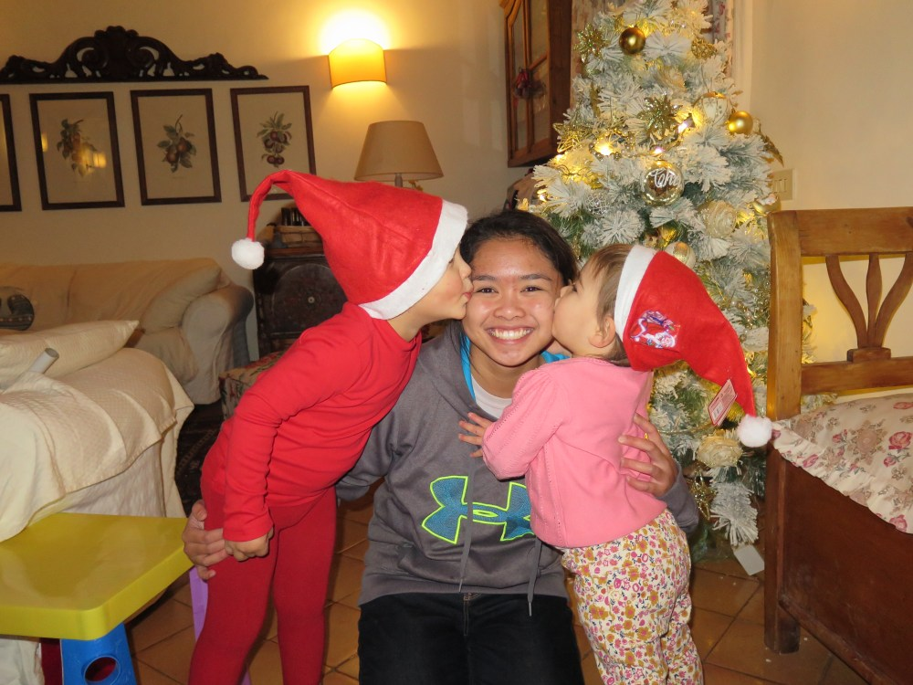 mother hugging two younger children in santa outfits with xmas tree behind