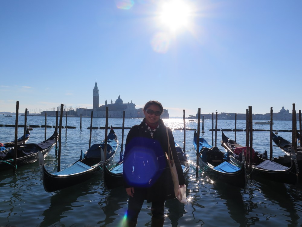 smiling girl standing in front of gondolas in venice
