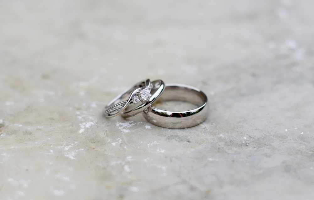 diamond engagement ring on top of two silver wedding bands