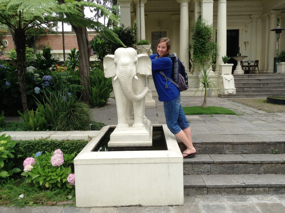 happy, smiling girl leaning against elephant statue