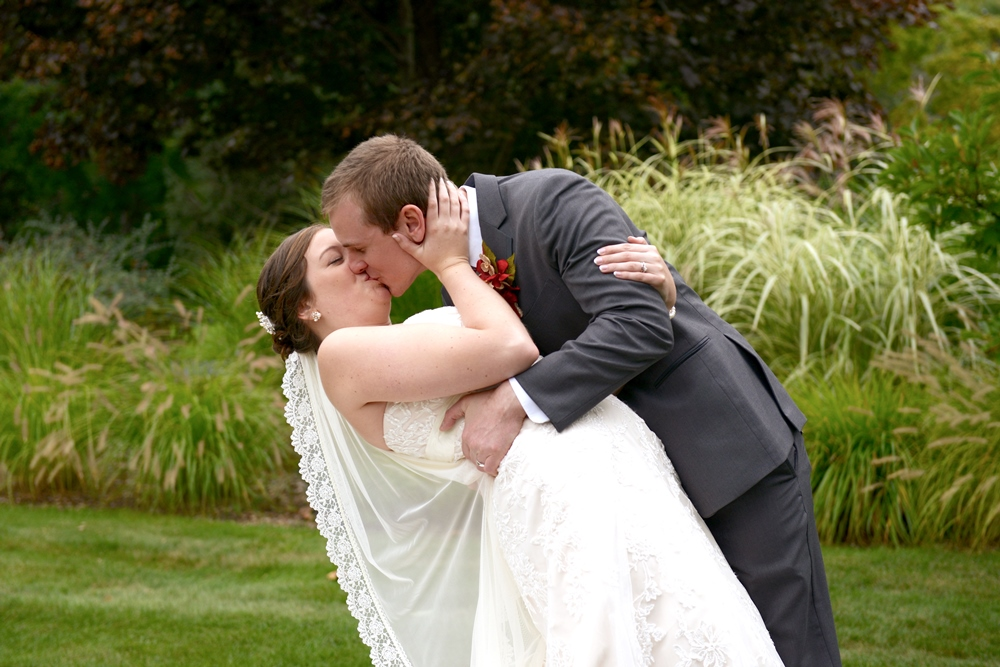 bride being hugged and kissed by groom