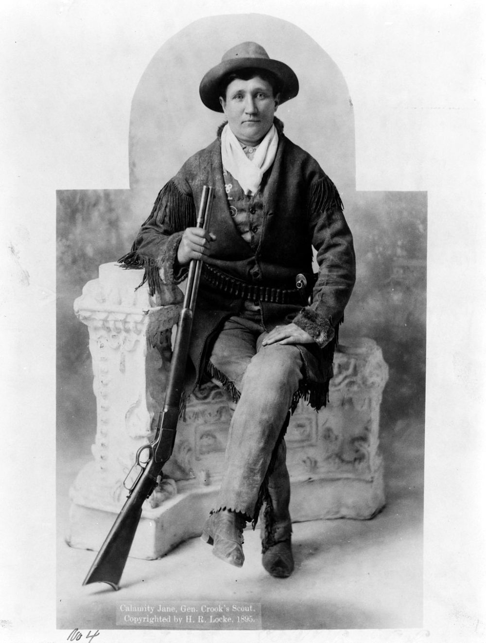 black and white image of calamity jane with shotgun sat on chair