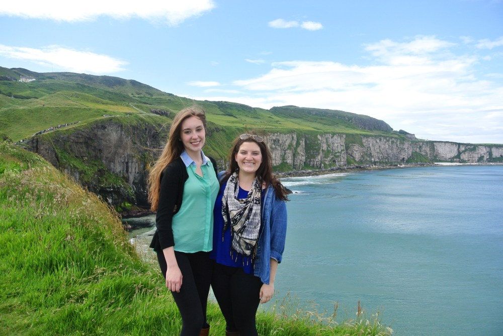 Two smiling girls standing on Carrick-a-Rede rope bridge in Ireland