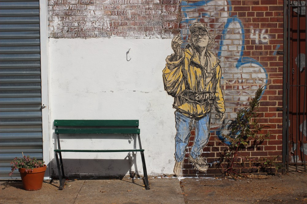 bench in front of street art on wall