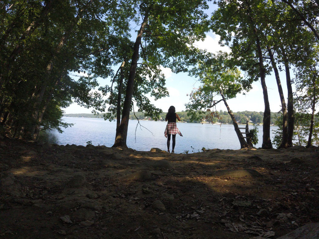 view of brunette girl standing on riverbank through trees looking out to the water