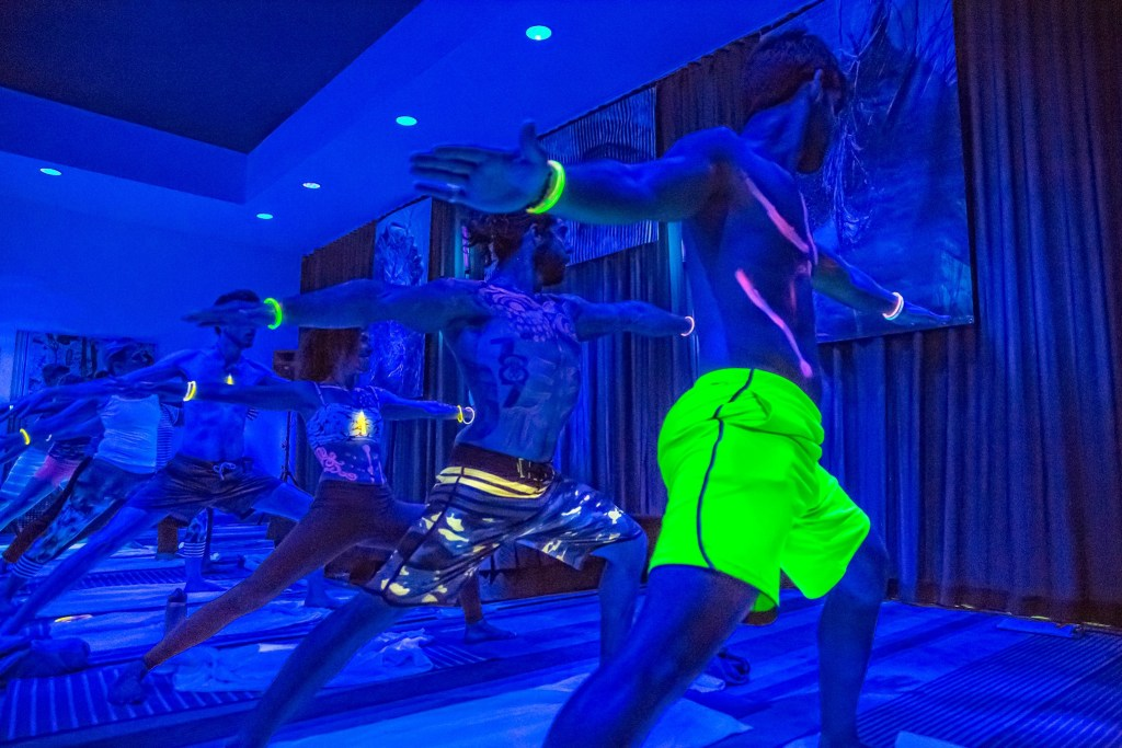 people practicing yoga in glow in the dark blue room