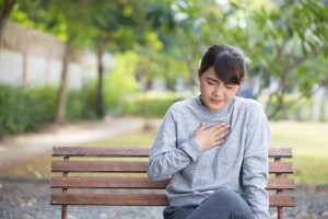 woman suffering from GERD at the park