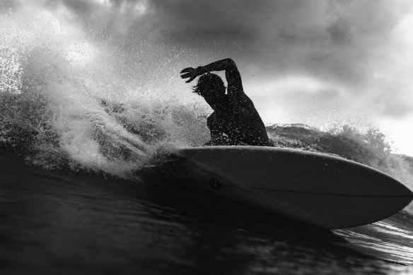silhouette of unrecognizable surfer on board