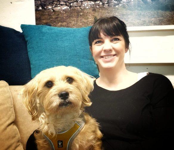 Jennie Toracca sitter i soffan på Glada Jyckar med en av sina hundar Torsten.