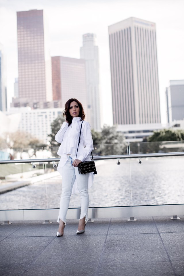 Fashion Blogger Maryam Nia wearing white ripped distressed jeans and ruffle bold white shirt in downtown LA