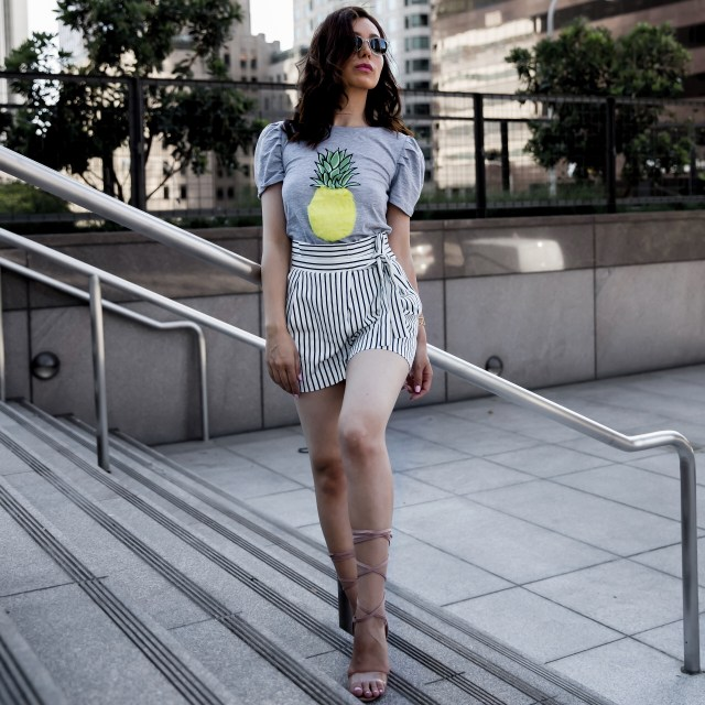 Fashion blogger wearing a yellow pineapple top with high waisted white shorts and lace up heels