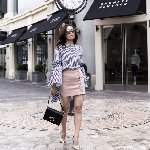 Fashion Blogger from Glam and Posh wearing striped top with statement sleeves with a blush tone mini skirt from Chicwish at the grove in LA