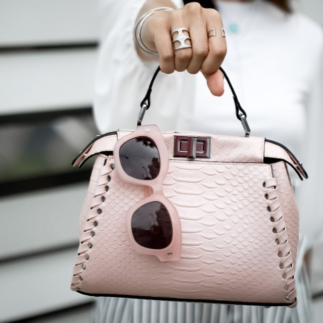 fashion blogger wearing statement glasses and blush pink bag