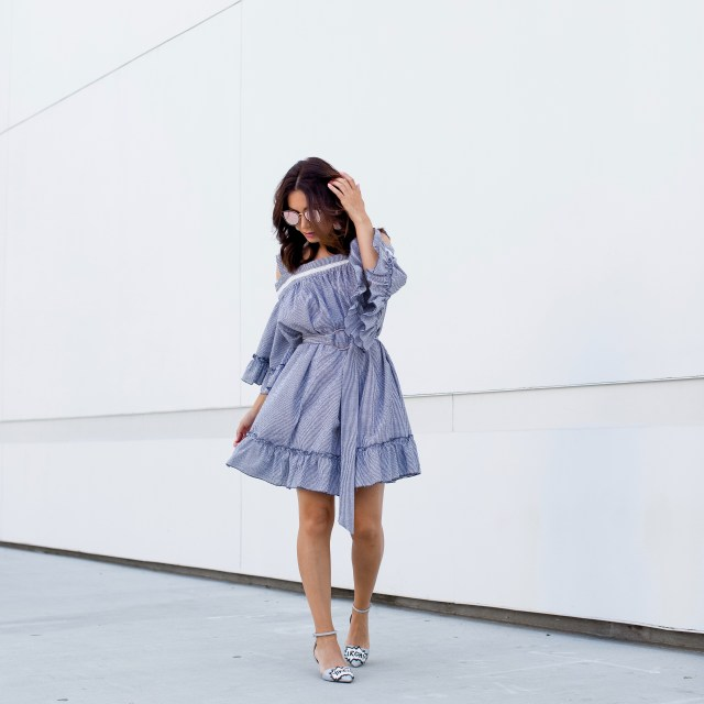 Fashion blogger wearing a ruffle summer dress with statement earrings