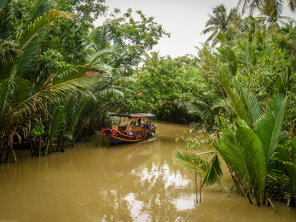 Boat gliding down the muddy waters of the Mekong delta