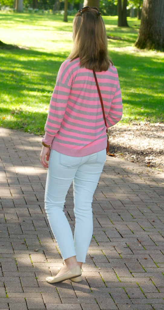 Striped pink and brown sweater with light denim pants