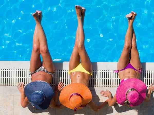 21378186 – three women in bikini wearing a straw hat by the swimming pool