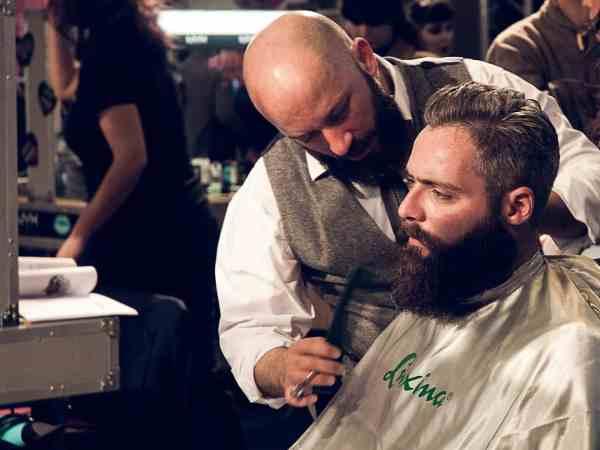 Barbier kämmt Bart eines Mannes