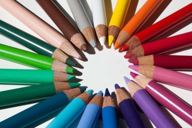 Buntstifte in vielen bunten Farben im Kreis auf weißem Untergrund