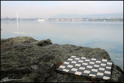 Il faut être Suisse pour apprécier les Echecs sur les bords du lac Léman... Taillé à même la pierre. (Petit matin calme, en arrière-arrière plan: le Jet d'eau, Genève, avril 2003.)