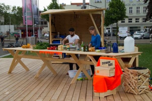 Projekt meyouwedo vor dem Grassimuseum. Zu sehen sind zwei Personen, die gemeinsam Essen vorbereiten