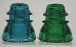 "Two Hemingray-42 glass insulators, in ""Hemingray Blue"" and a medium shade of true green."