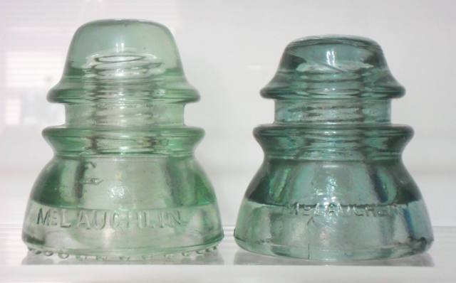 "Two CD 154 ""McLAUGHLIN / NO. 42"" variants. The light green example on left has round drip points, the sage-gray green insulator on  right has a smooth base.  This style was a competitor to the ubiquitous ""HEMINGRAY-42"" made by Hemingray Glass Company."