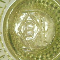 """B in a diamond"" mark on inside of Star & Dewdrop master salt dish in vaseline glass, made in 1994. This mark has 3 lines outside the diamond, indicating production between 1993-1998."