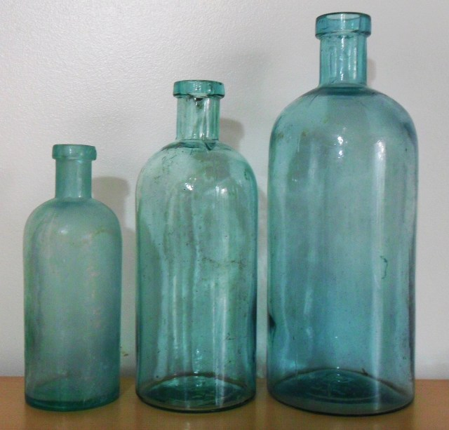 """Group of three F.C.G.CO. """"generic"""" chemical or packer bottles. 6 inches, 7.5 inches and 9 inches in height."""