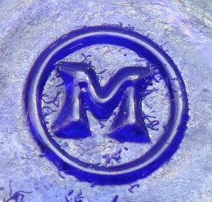 """M in a circle"" mark used by Maryland Glass Corporation. Here, as embossed on the base of a small cobalt blue Bromo-Seltzer bottle."