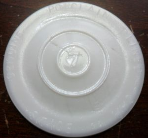 """Opaque white disc with mold number """"7"""" placed in the center."""
