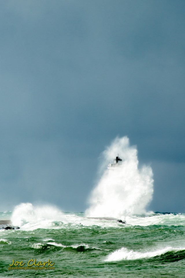 A large wave breaks over the Ludingotn Light, by Joe Clark www.glasslakesphotography.com