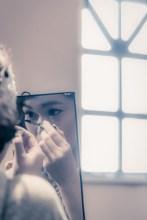 手鏡でメイクをする花嫁