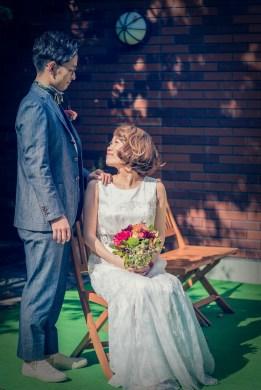 座った花嫁の肩に優しく手を置く新郎