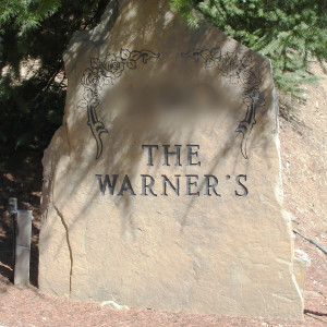 "This is a photo of a rock marker by a driveway. It reads, ""The Warner's."""