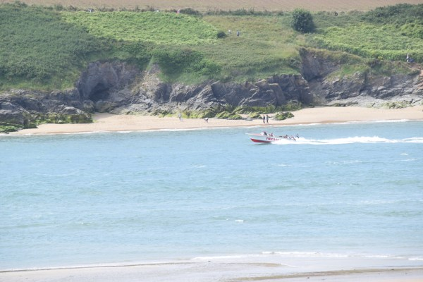 Red and white Padstow speedboat tearing down the Camel estuary