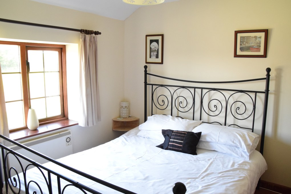 Kingsize bedroom in Glen Valley holiday cottage with black metal framed bed and white linen, window overlooking the rear garden