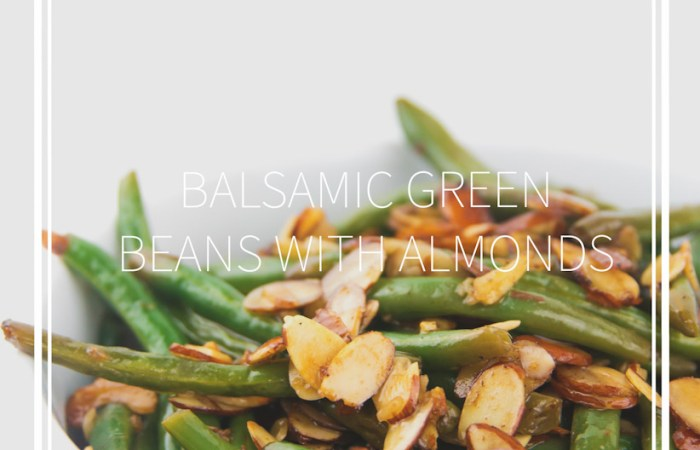 a white bowl of cooked balsamic green beans with almonds on top