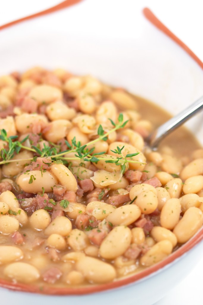 up close shot of ham and bean soup in a white bowl with thyme on top