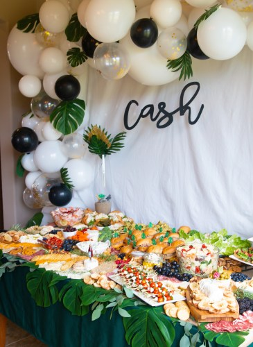 balloon arch with white backdrop with a grazing table full of food