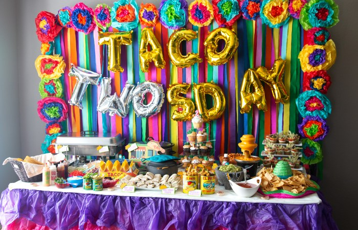 streamer back drop with mexican flowers border wih taco twosday balloons with mexican food table
