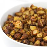 white bowl of roasted zesty italian potatoes with parsley sprinkled on top